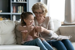Senior grandmother teaches little granddaughter to knit seated on couch, multi generational people loving family holding needles and yarn, hobby and fun, activity to improve fine motor skills concept
