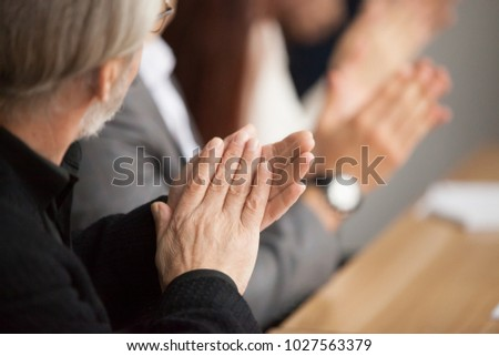 Senior gray-haired businessman clapping hands attending conference, aged training participant applauding at group meeting, old man expressing appreciation or congratulation, rear view, focus on hands