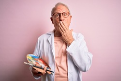 Senior grey haired artist man painting using painter palette over pink background cover mouth with hand shocked with shame for mistake, expression of fear, scared in silence, secret concept