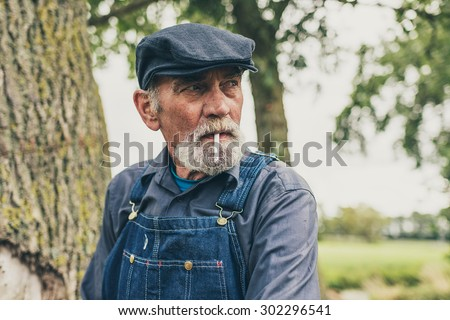 Senior grey-haired bearded country farmer standing smoking in his cloth cap and denim dungarees as he stares thoughtfully into the distance