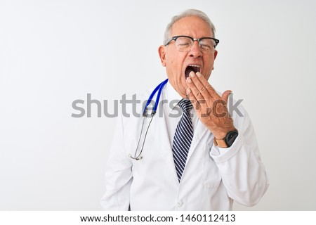 Senior grey-haired doctor man wearing stethoscope standing over isolated white background bored yawning tired covering mouth with hand. Restless and sleepiness.