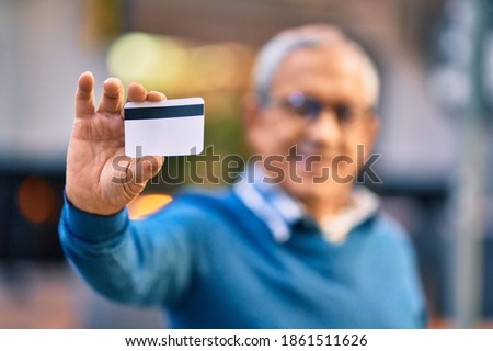 Senior grey-haired man smiling happy holding credit card at the city. Foto stock ©