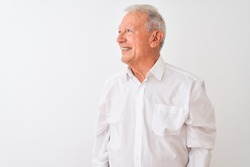 Senior grey-haired man wearing elegant shirt standing over isolated white background looking away to side with smile on face, natural expression. Laughing confident.