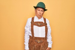 Senior grey-haired man wearing german traditional octoberfest suit over yellow background skeptic and nervous, frowning upset because of problem. Negative person.