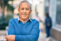 Senior grey-haired man with arms crossed smiling happy standing at the city.