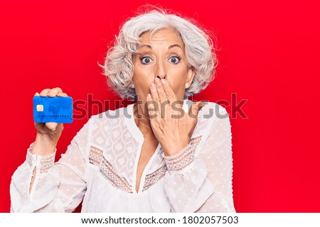 Senior grey-haired woman holding credit card covering mouth with hand, shocked and afraid for mistake. surprised expression  Photo stock ©