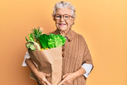 Senior grey-haired woman holding paper bag with bread and groceries looking positive and happy standing and smiling with a confident smile showing teeth