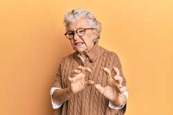 Senior grey-haired woman wearing casual clothes and glasses disgusted expression, displeased and fearful doing disgust face because aversion reaction. with hands raised