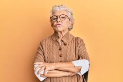 Senior grey-haired woman wearing casual clothes and glasses skeptic and nervous, disapproving expression on face with crossed arms. negative person.