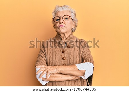 Senior grey-haired woman wearing casual clothes and glasses skeptic and nervous, disapproving expression on face with crossed arms. negative person.  Сток-фото ©
