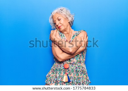 Senior grey-haired woman wearing casual clothes hugging oneself happy and positive, smiling confident. self love and self care  Сток-фото ©