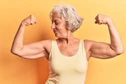 Senior grey-haired woman wearing casual clothes showing arms muscles smiling proud. fitness concept.