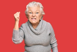 Senior grey-haired woman wearing casual winter sweater angry and mad raising fist frustrated and furious while shouting with anger. rage and aggressive concept.