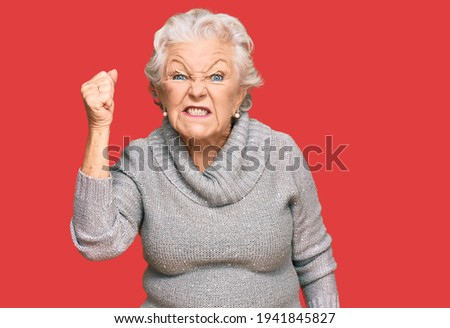 Senior grey-haired woman wearing casual winter sweater angry and mad raising fist frustrated and furious while shouting with anger. rage and aggressive concept.  Сток-фото ©