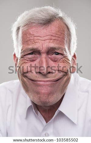 Senior grinning from ear to ear. Humorous portrait of a retired gray haired senior man with a wide beaming smile that epitomises the idiom, grinning from ear to ear