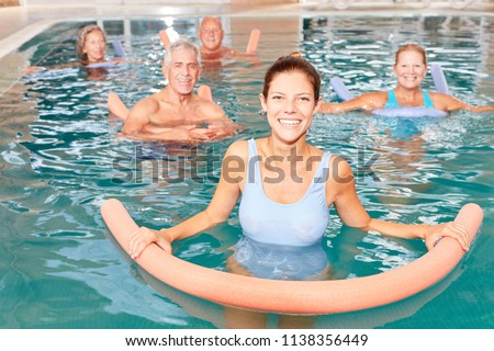 Senior group doing water aerobics in pool with young physiotherapist
