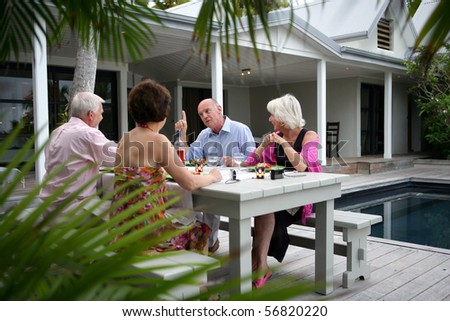 Senior group having a dinner on a terrace near a swimming pool