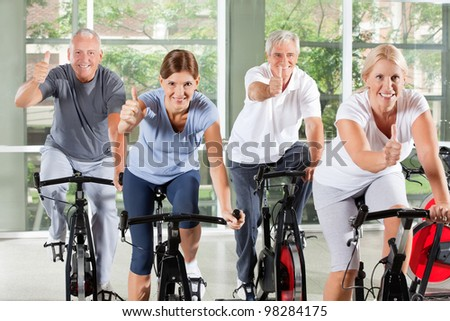 Senior group on bikes in gym holding thumbs up