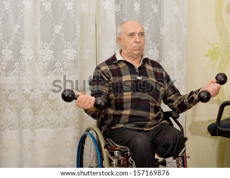 Senior handicapped male amputee sitting in his wheelchair doing exercises working out with a pair of dumbbells
