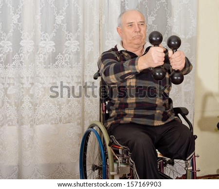 Senior handicapped man exercising with a pair of dumbbells to strengthen his arms while sitting in a wheelchair