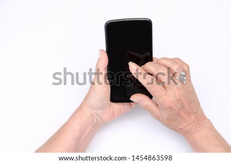 Senior hands using mobile phone,top view.Old matured female hand touch black smart phone screen.Isolated on white background
