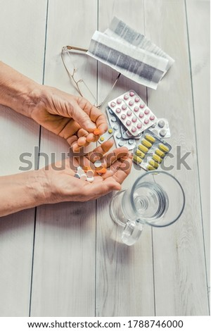 Senior hands with pills and drugs on table, glass of water. Wrinkled hands of old woman holding colorful tablets, glasses and prescription wooden background. Old age. Health care for the elderly. stock photo