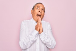 Senior handsome grey-haired man wearing elegant shirt over isolated pink background begging and praying with hands together with hope expression on face very emotional and worried. Begging.