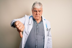 Senior handsome hoary doctor man wearing coat and stethoscope over white background looking unhappy and angry showing rejection and negative with thumbs down gesture. Bad expression.