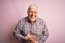 Senior handsome hoary man wearing casual colorful shirt over isolated pink background smiling and laughing hard out loud because funny crazy joke with hands on body.