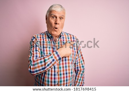 Senior handsome hoary man wearing casual colorful shirt over isolated pink background Surprised pointing with finger to the side, open mouth amazed expression. ストックフォト ©