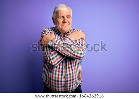Senior handsome hoary man wearing casual colorful shirt over isolated purple background Hugging oneself happy and positive, smiling confident. Self love and self care Сток-фото ©