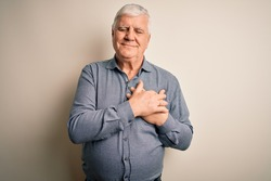 Senior handsome hoary man wearing casual shirt standing over isolated white background smiling with hands on chest with closed eyes and grateful gesture on face. Health concept.