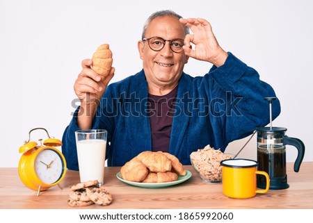 Senior handsome man with gray hair sitting on the table eating croissant for breakfast doing ok sign with fingers, smiling friendly gesturing excellent symbol  Stock fotó ©