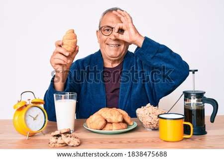 Senior handsome man with gray hair sitting on the table eating croissant for breakfast smiling happy doing ok sign with hand on eye looking through fingers  Stock fotó ©