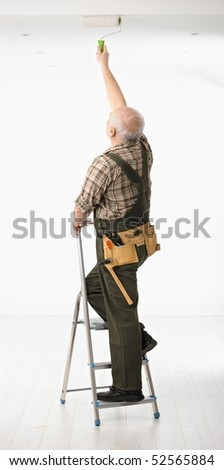 Senior handyman standing on ladder painting the ceiling in white room.