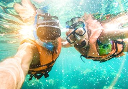Senior happy couple taking selfie in tropical sea excursion with water camera - Boat trip snorkeling in exotic scenarios - Active retired elderly and fun concept on scuba diving - Warm vivid filter