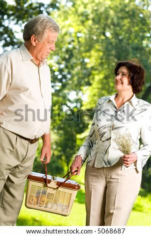 Senior happy couple walking together, carrying picnic basket