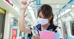 senior high school student girl use mobilephone when commute on mrt and wear face mask