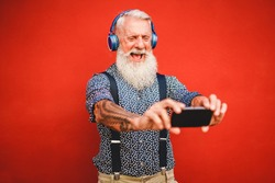 Senior hipster man using smartphone app for creating playlist with rock music - Trendy tattoo guy having fun with mobile phone technology - Tech and joyful elderly lifestyle concept - Focus on face