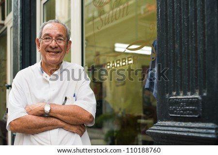 senior hispanic barber in old fashion barber's shop, posing and looking at camera with arms crossed near shop window