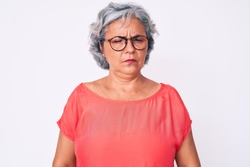 Senior hispanic grey- haired woman wearing casual clothes and glasses skeptic and nervous, frowning upset because of problem. negative person.