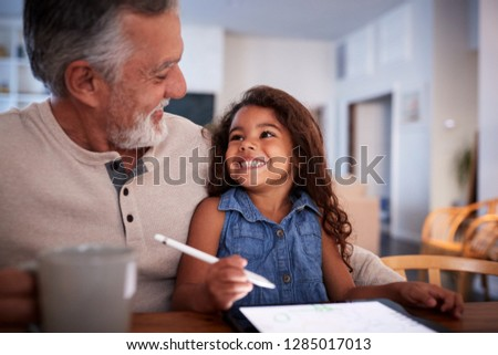 Senior Hispanic man with his granddaughter using tablet computer, looking at each other, close up