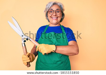 Senior hispanic woman wearing gardener apron and gloves holding shears looking positive and happy standing and smiling with a confident smile showing teeth  Photo stock ©
