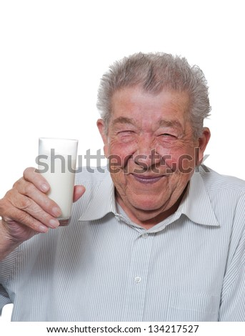 Senior holds happy a glass of milk in hand