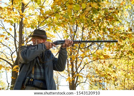 Senior hunter in forest aim his rifle at animal, trophy #1543120910
