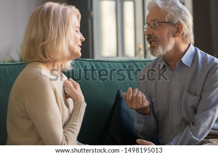 Senior husband and wife sit on couch at home talk dispute on family relations problem, stubborn mature couple having disagreement misunderstanding speak discuss health troubles or relationships Stock photo ©