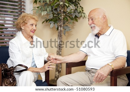 Senior husband and wife wait together and holding hands in the doctors waiting room.
