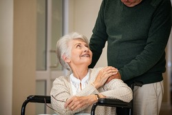 Senior husband comforting woman on a wheelchair by holding hand and looking at her at nursing home. Old man pushing handicapped woman sitting on a wheelchair in the corridors of the medical clinic.