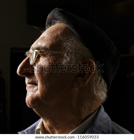 Senior in cap and eyeglasses sideview head and shoulders portrait