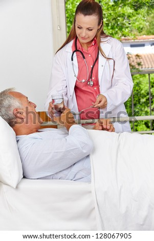 Senior in hospital taking medicine with a glass of water